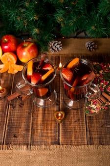 Vin brulè di natale con frutta, candele e spezie sulla tavola di legno.