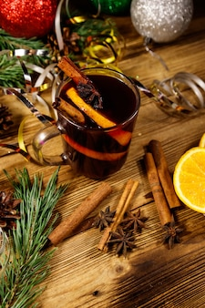 Vin brulé di natale con spezie e decorazioni natalizie su tavola di legno