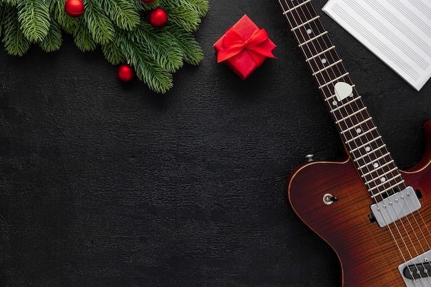 Composizione di musica di natale con chitarra e rami di abete