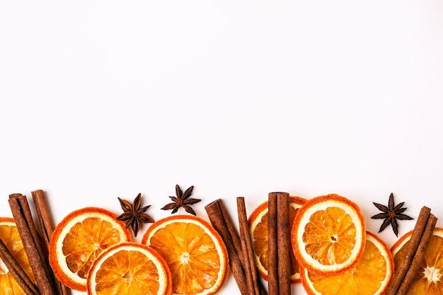 Bordo della natura di natale di fette di arance secche e bastoncini di cannella.