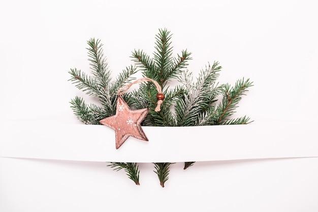 Natale composizione floreale neutra di rami di abete e palline di legno a stella.
