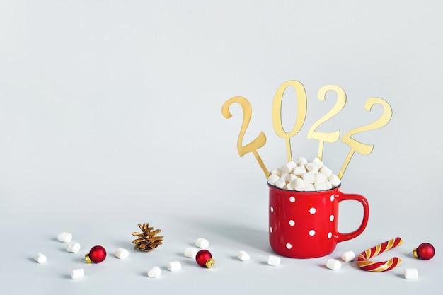 Concetto di natale o capodanno 2022. tazza rossa di cacao con marshmallow e numeri d'oro 2022, copia spazio.