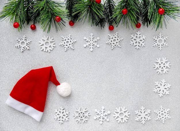 Natale capodanno sfondo rami di abete fiocchi di neve cappello di babbo natale su sfondo con paillettes