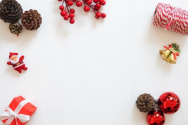 Natale e capodanno sfondo. struttura di decorazione natalizia con coni di pino, bacca di agrifoglio, palline di natale, rotolo di corda, regalo. disegno piatto piano creativo, disegno a vista superiore