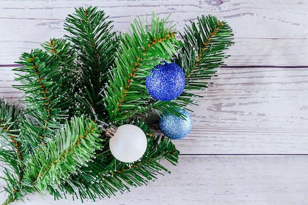 Sfondo di natale o capodanno: albero di pelliccia, rami, palline di vetro colorate e giocattoli, regali, decorazioni su un bianco
