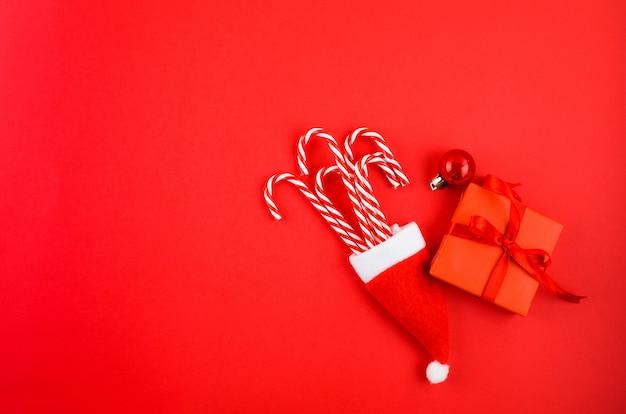 Sfondo di natale o capodanno confezione regalo caramelle caramelle e decorazioni su sfondo rosso