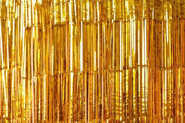 Sfondo di natale, capodanno e trama di orpelli d'oro o nastri lucidi