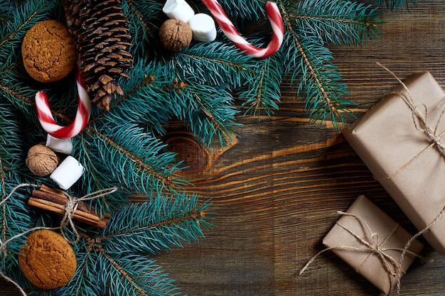 Sfondo di natale o capodanno con biscotti spezie noci di cannella e ramo di abete su legno scuro...