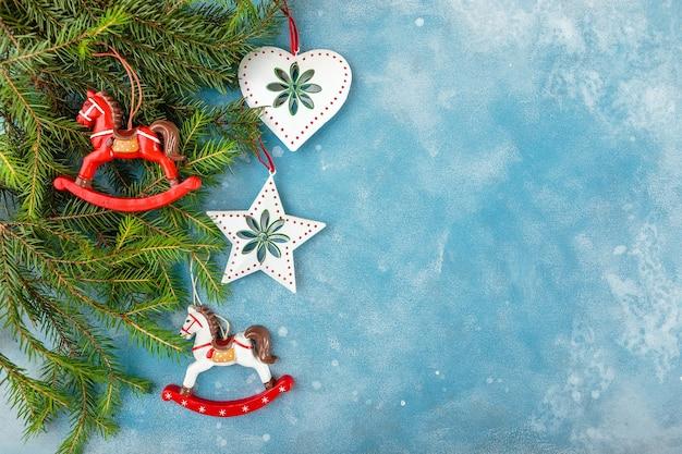 Sfondo blu di natale e capodanno con rami di abete e giocattoli di natale - cavalli, una stella e un cuore. vista dall'alto