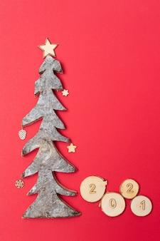 Cartolina di natale e capodanno con numeri in legno 2021 e albero di natale in legno su sfondo rosso.