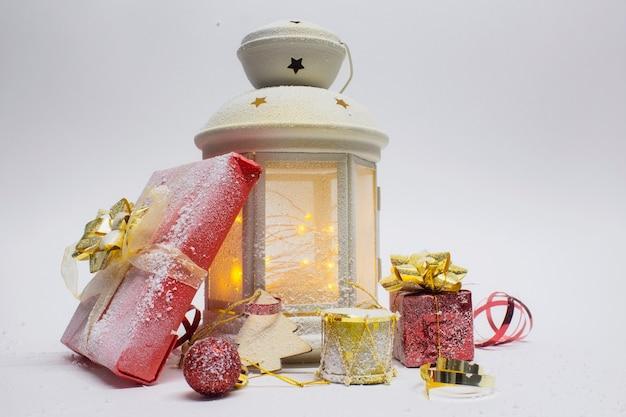 Composizione di natale e capodanno. lanterna incandescente festosa con decorazioni, regali e fiocchi luminosi su sfondo bianco.