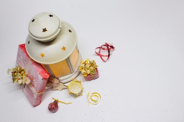 Composizione di natale e capodanno. lanterna luminosa festiva con decorazioni, regali e fiocchi luminosi