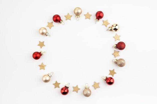 Composizione di natale o capodanno. cornice rotonda fatta di decorazioni natalizie su sfondo bianco con copia spazio per il testo. laici piatta.
