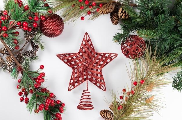 Composizione nel nuovo anno di natale su priorità bassa bianca con una stella rossa. rami di abete, decorazioni natalizie. appartamento laico, vista dall'alto, copia dello spazio.
