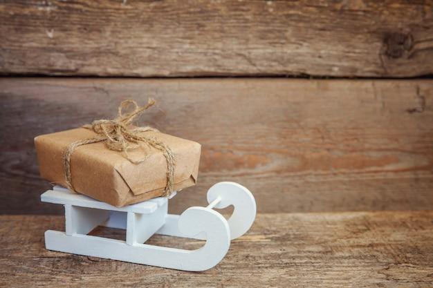 Natale capodanno composizione inverno oggetti confezione regalo e slitta su fondo in legno