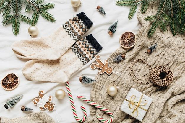 Composizione del nuovo anno di natale. calzini di lana, scatola regalo, rami di abete, palline di natale, biscotti allo zenzero, caramelle in stick, plaid lavorato a maglia, decorazioni