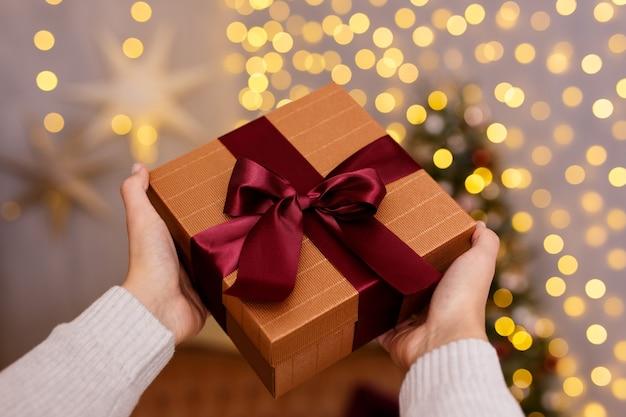 Concetto di natale e capodanno - chiusura della confezione regalo in mani maschili su sfondo di luci a led festive
