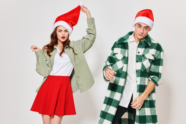 Coppia di natale capodanno innamorato in cappelli festivi su sfondo chiaro. foto di alta qualità