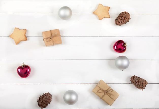 Decorazione di natale e capodanno di palline, coni di cedro, biscotti, regali e cuori su una superficie di legno bianca
