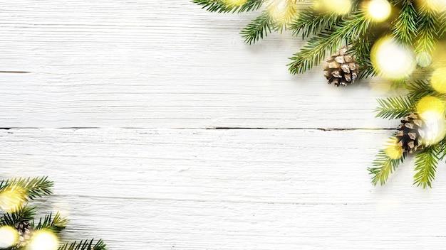 Decorazione di natale e capodanno su fondo di legno bianco con luci dorate d'ardore di ang di rami di abete.