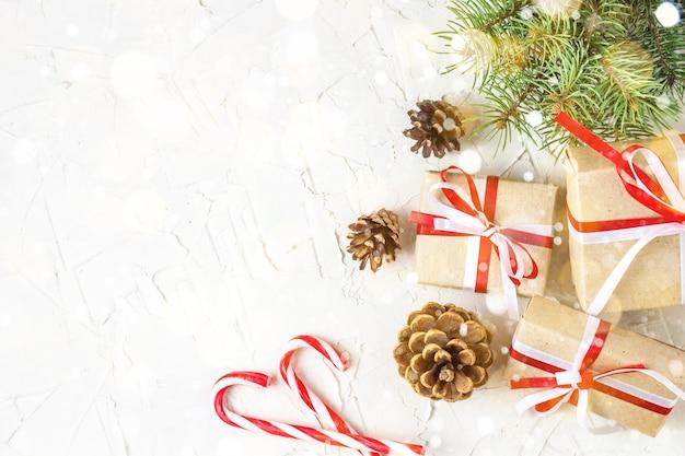 Sfondo di decorazioni di natale o capodanno con pigne, rami di abete, scatole regalo e bastoncini di zucchero. bokeh tonico e neve