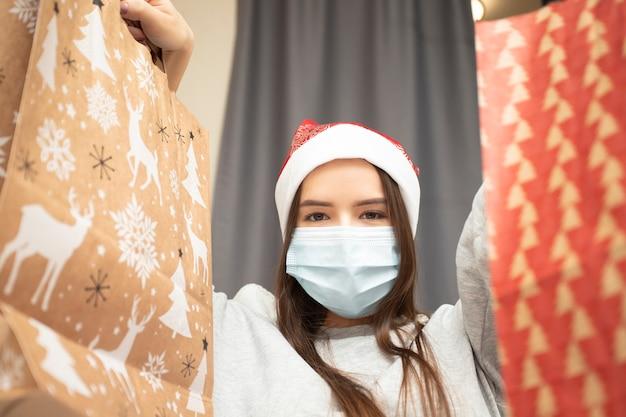 Natale e capodanno durante la pandemia di coronavirus. la ragazza con la maschera raccoglie i regali a casa