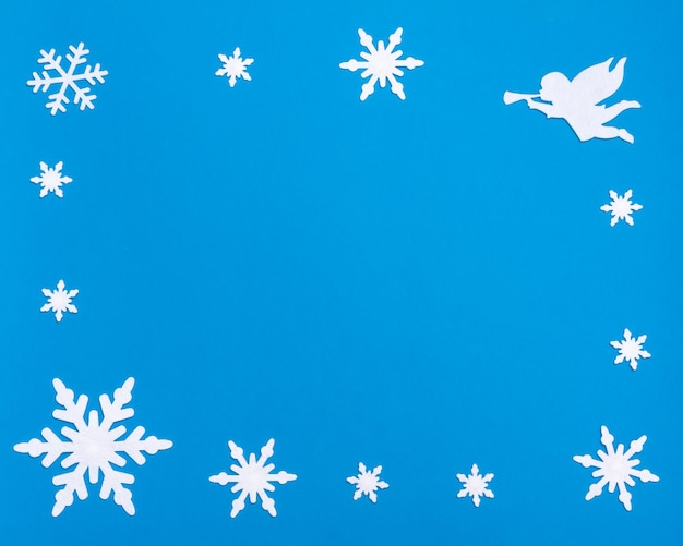 Composizione piatta di natale e capodanno con blocco note in bianco bianco, campana blu, angelo bianco che suona la tromba e fiocchi di neve su sfondo blu