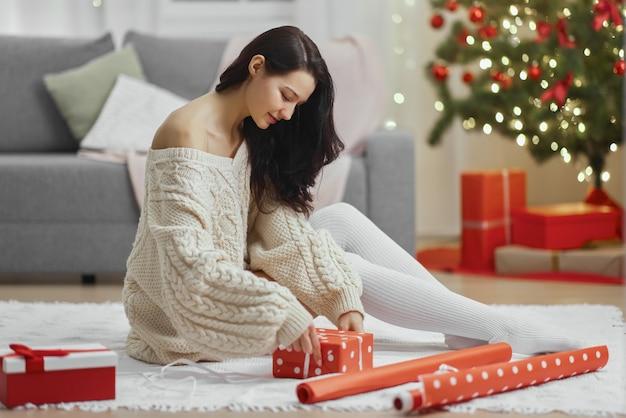 Confezione regalo di natale e capodanno da parte di una donna a casa durante le vacanze invernali