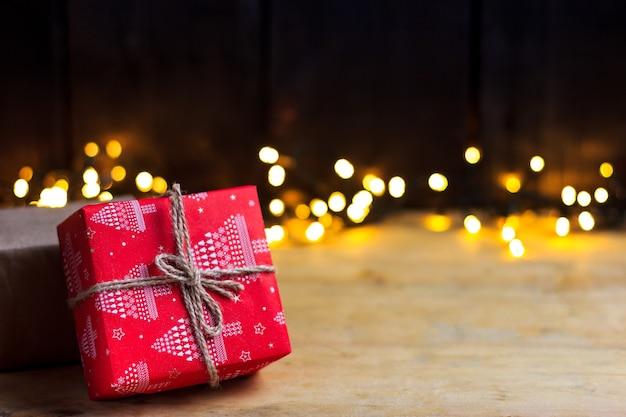 Regali di natale per il nuovo anno su un tavolo in legno chiaro con luci a ghirlanda