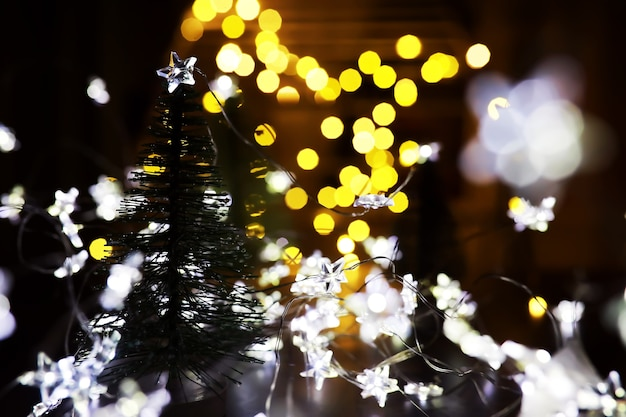 Fondo di festa di natale e capodanno con spazio di copia. sfondo vacanza invernale con abete congelato, luci glitterate, bokeh.