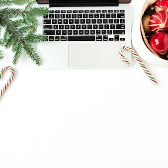 Composizione di festa di natale capodanno. area di lavoro scrivania da casa con laptop, palline di natale, rami di abete, bastoncini di zucchero su bianco