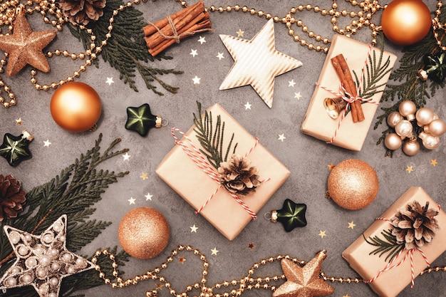 Decorazioni per le vacanze di natale e capodanno nei colori verde e dorato su sfondo di cemento grigio.