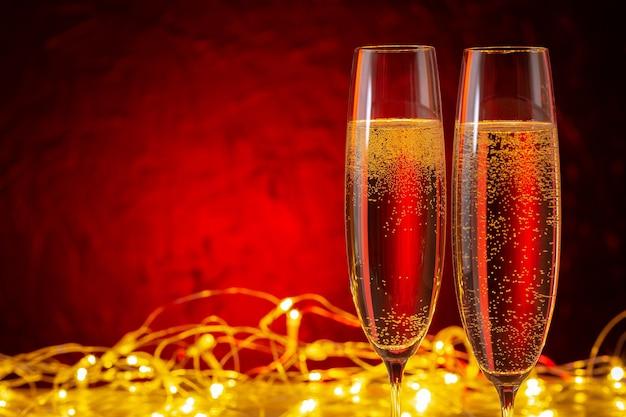 Sfondo di vacanze di natale e capodanno. bicchieri di champagne e luminarie con copia spazio.