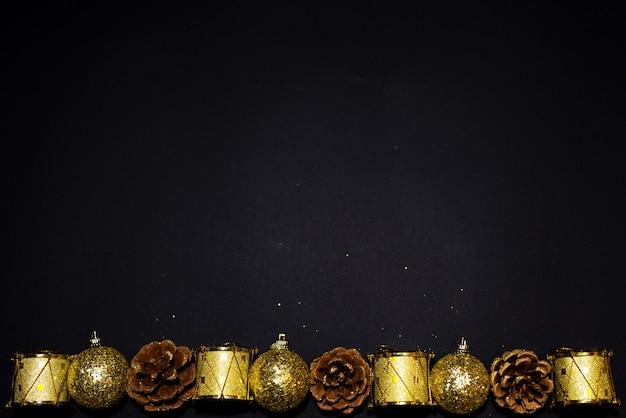 Vacanze di natale e capodanno sfondo nero con palline d'oro, coni di abete rosso, tamburi