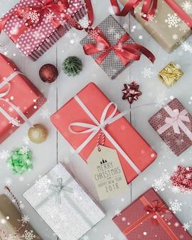 Contenitore di regalo di feste del nuovo anno e di natale sulla tavola di legno bianca con effetto della neve di caduta disposizione piana con il segno 2018 di buon natale & del buon anno concetto di congratulazioni e di giri.