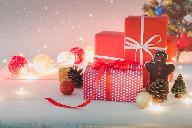 Contenitore di regalo di feste del nuovo anno e di natale con l'ornamento decorativo sulla tavola di legno bianca con effetto della neve di caduta fondo dell'albero di natale concetto di congratulazioni e di giri.