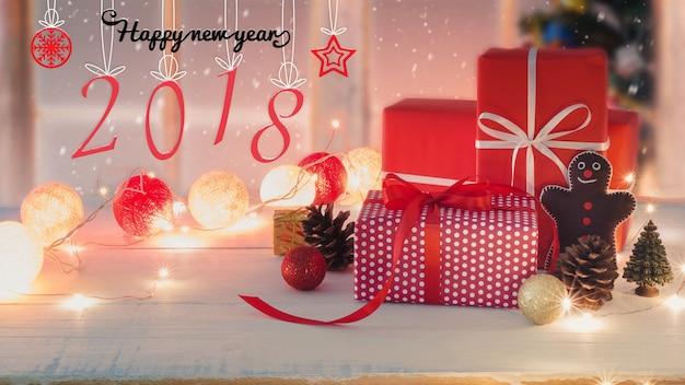 Contenitore di regalo di feste di natale e capodanno con ornamento decorativo sulla tavola di legno bianco