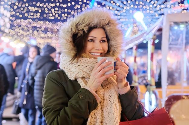Vacanze di natale e capodanno, bella donna matura felice con borse della spesa e tazza di bevanda calda al mercatino di natale