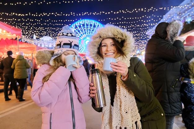 Vacanze di natale e capodanno, mamma felice e figlia bambino che camminano insieme bevendo una tazza di tè caldo al mercatino di natale