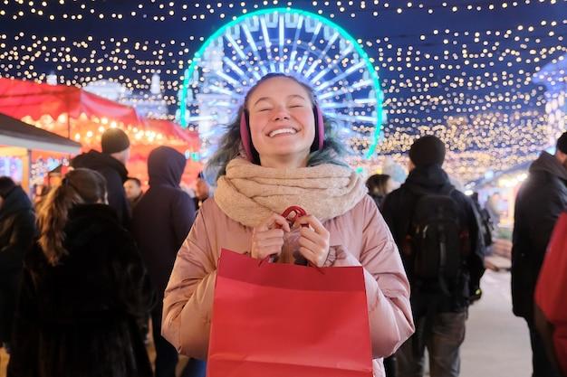 Vacanze di natale e capodanno, ragazza adolescente felice con borse della spesa rosse al mercatino di natale