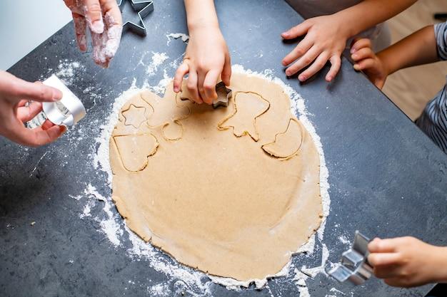 Vacanze di natale e capodanno, mamma e bambini preparano i biscotti di pan di zenzero