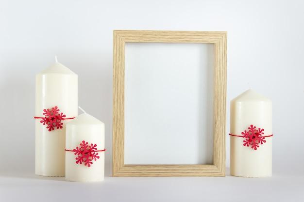 Natale, modello di mockup di capodanno con cornice in legno e tre candele bianche con fiocchi di neve in legno rossi su sfondo bianco.