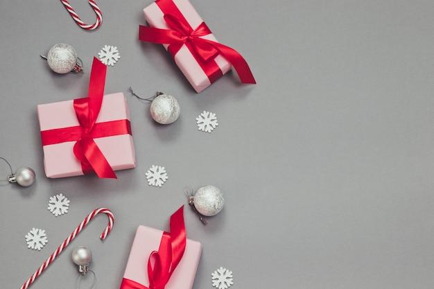 Regali di natale o capodanno di carta rosa e nastri ren, bastoncini di zucchero, coriandoli e palline d'argento su sfondo grigio.