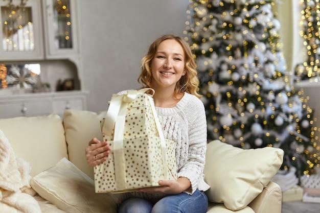 Regali di natale e capodanno. felice giovane signora che tiene e abbraccia la confezione regalo, seduta sul divano di casa nel soggiorno