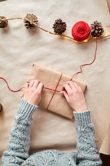 Regali di natale e capodanno per le vacanze. prenota come regalo, lo avvolge in carta artigianale e lo fascia con una corda rossa