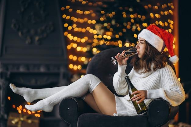 Natale, capodanno. bella donna in maglione caldo seduto sulla sedia con champagne