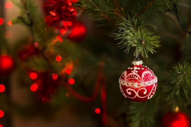 Natale o capodanno palla decorativa rossa su un albero addobbato a festa muro di natale selective soft focus bokeh