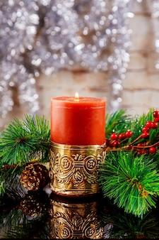 Composizione scura di natale o capodanno con candele rosse accese, rami di abete, pigne, fiocchi di neve e bacche su sfondo di legno vecchio, immagine tonica, messa a fuoco selettiva