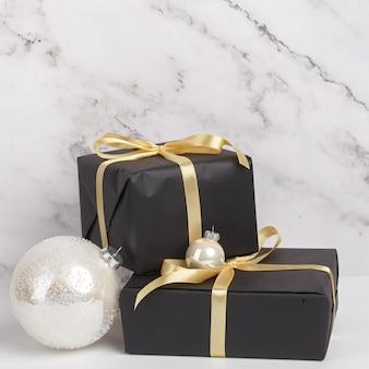 Composizione di vigilia di capodanno di natale. scatole di regali e decorazioni natalizie su fondo in marmo bianco