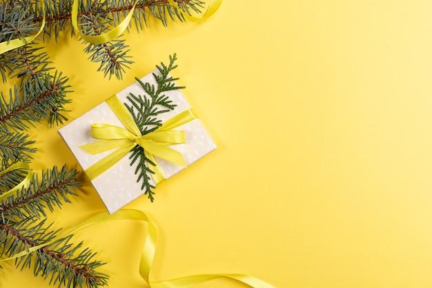 Natale, capodanno, san valentino sfondo giallo brillante con confezione regalo fai da te e rami di abete verde decorati con nastro giallo. vista dall'alto. orientamento orizzontale. copia spazio per il testo.